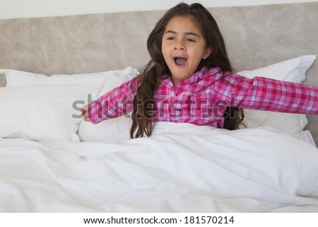 Young girl yawning while stretching her arms in bed at home - stock photo