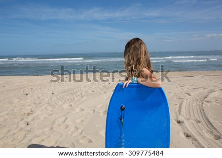 Young girl 10 years old with a body board at the beach - stock photo