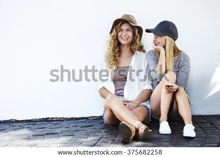 Young girlfriends laughing together - stock photo