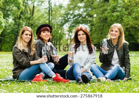 Young girls are sitting in the park and holding a bottle of water.Refreshment for young girls