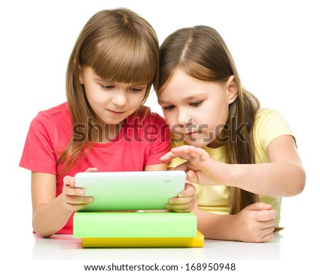 Young girls are using tablet while sitting at table, isolated over white - stock photo