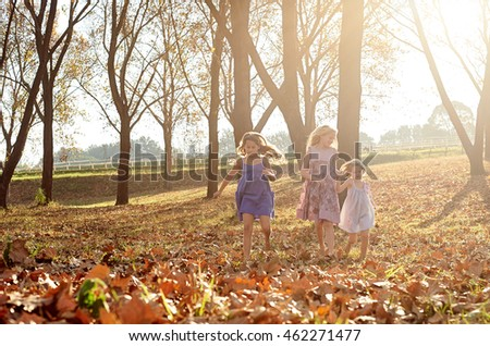 Young girls children kids playing running in fallen autumn leaves
