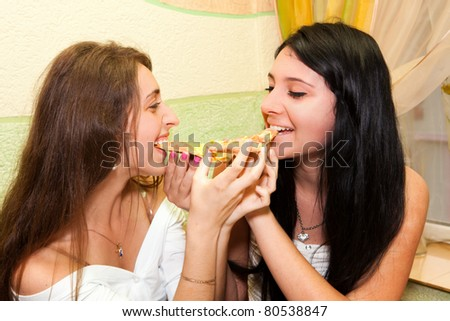 Young girls eating pizza - stock photo