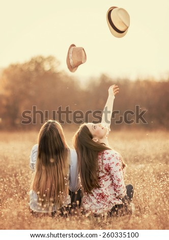Young girls having fun outside, throwing hats up and smile - stock photo