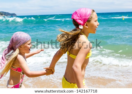 Young girls having fun together at sea. - stock photo