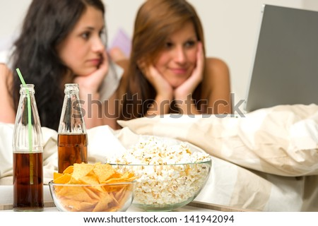 Young girls having slumber party and watching movies - stock photo