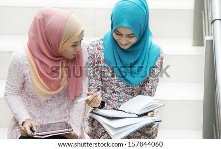 Young Girls in scarf are having some discussions about subject.