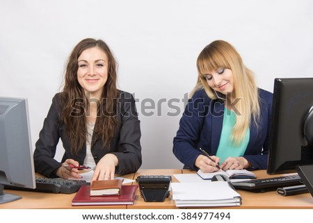 Young girls in the office, one looks in the frame, the second talking on the phone and writing in diary