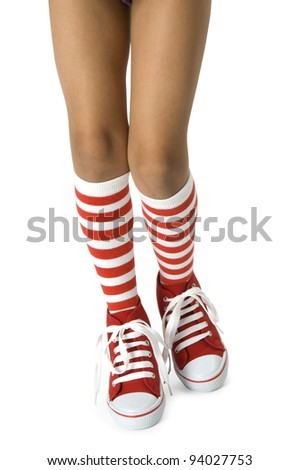 Young girls legs wearing long red striped socks with red shoes on a white background. Clipping path included. - stock photo
