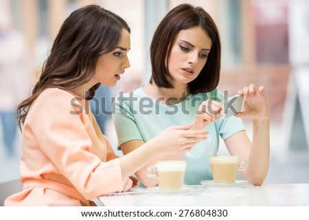Young girls looking to the phone and feeling upset while sitting  in urban cafe. - stock photo