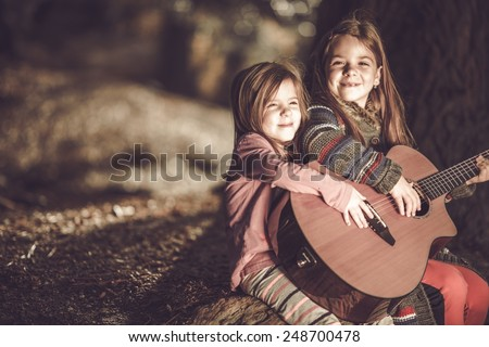 Young Girls Playing Acoustic Guitar in the Park. Children and the Music Concept. - stock photo