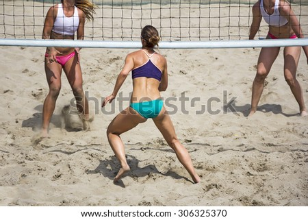 Young girls playing Beach Volleyball in sunny day - stock photo