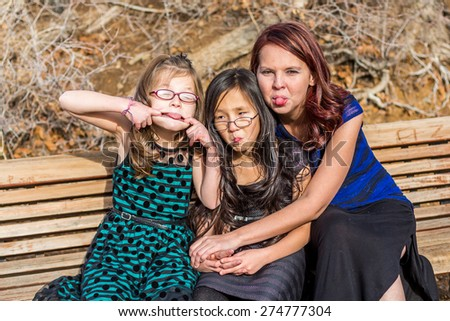 Young girls playing with their mother at a park in Reno, Nevada, USA.