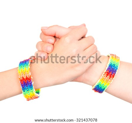 young girls shaking hands with a bracelet patterned as the rainbow flag. isolated on white background