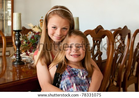 Young girls sitting at wood finished dining room table with decorations - stock photo
