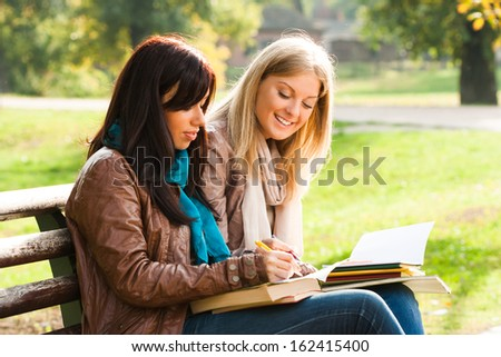 Young girls sitting in the park and learning,Students - stock photo
