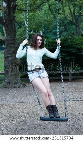 Young girls standing on the swings in the park, playing - stock photo