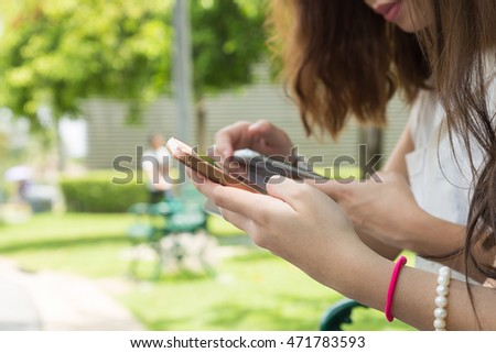 Young girls using smartphone with friend in park