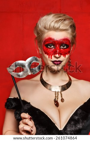 """Young girls with appliance make - up in the style of """"Halloween"""" in the studio on a red background - stock photo"""
