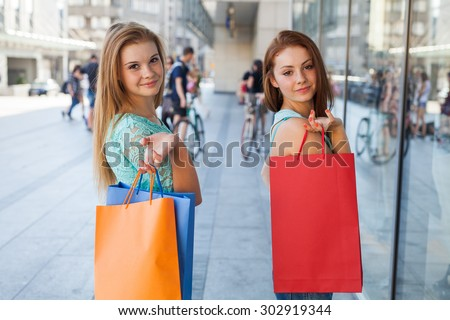 Young girls with colorful shopping bags. Season of sales