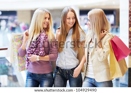 Young girls with shopping bags in shop - stock photo