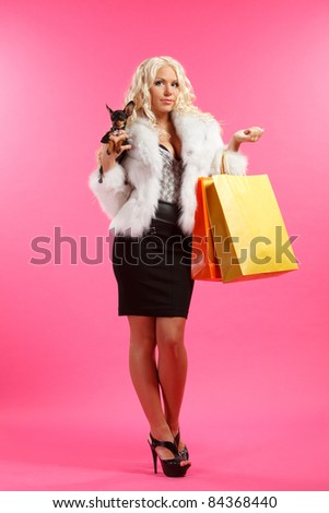 young glamorous blonde with shopping bags holding toy terrier dog against pink background - stock photo
