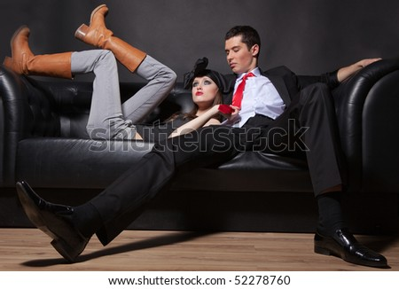 Young glamorous loving couple on a black sofa.