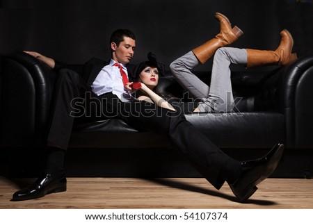 Young glamorous loving couple on black sofa. - stock photo