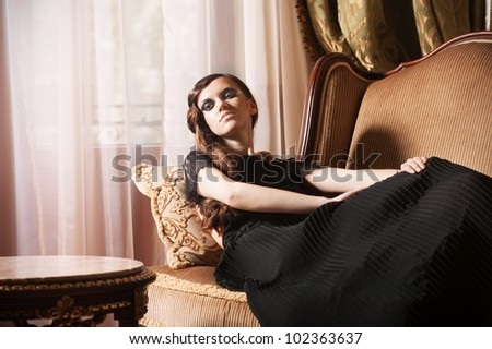Young glamour woman sitting on armchair