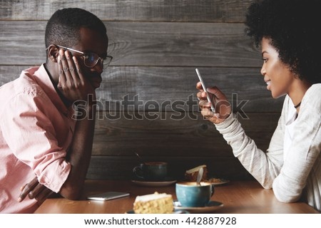 Young gloomy and bored African man getting angry while his cheerful dark skinned girlfriend chatting with her friends on social networks using mobile phone, instead of talking to him during the date - stock photo