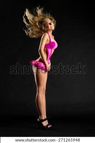 Young go-go dancer girl on black - stock photo