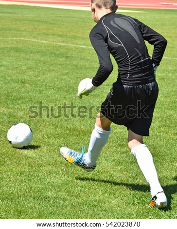 Young goalkeeper kicks the ball off