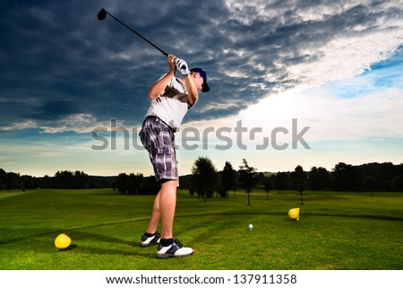 Young golf player on course doing golf swing, he presumably does exercise - stock photo