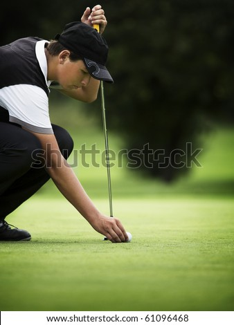 Young golf player squatting to put down ball at green. - stock photo