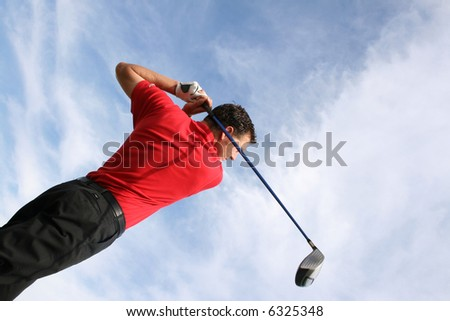 Young golfer at an angle, hitting a driver against a blue sky - stock photo