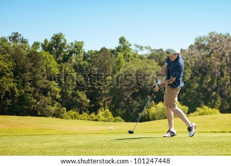 Young golfer driving the ball down the fairway with his golf wood