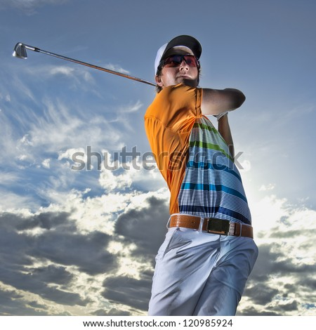 Young golfer hits an iron shot - stock photo