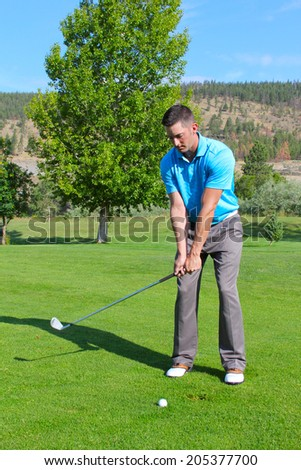 Young golfer hitting a shot with an iron  - stock photo