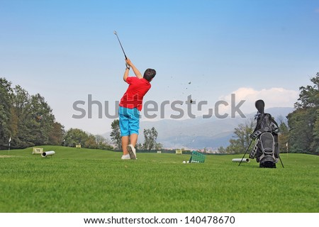 Young golfer impact exercise on green grass field