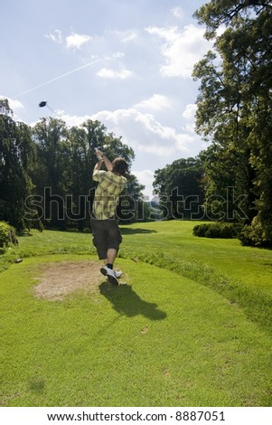 Young golfer on tee in the middle of swing - stock photo
