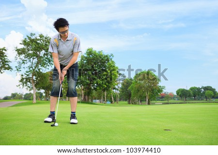 Young golfer putting on green - stock photo