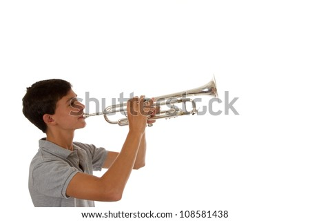 young good looking boy playing the trumpet with copy space - stock photo