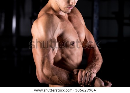 Young good looking caucasian muscular man working out in sports center, posing, showing strong biceps, chest muscles, close up, body sculpture concept - stock photo