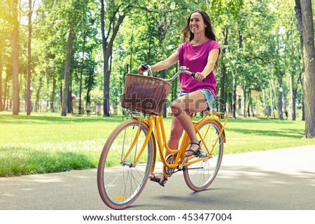Young good-looking female is enjoying her bicycle ride on the parkway on a sunny summer day  - stock photo