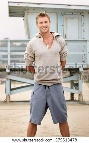 Young good looking male on beach with nice smile - stock photo