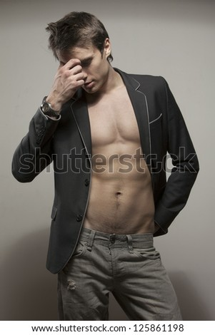 Young good-looking model  in dark suite  with naked torso - stock photo