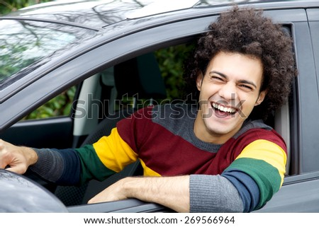 Young good looking modern man sitting in car laughing - stock photo