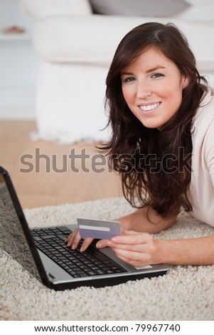 Young good looking woman making a payment with a credit card on the internet while lying on a carpet in the living room