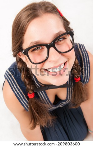 Young goofy and nerdy girl looking at camera. studio shot. - stock photo