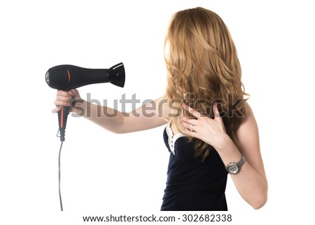 Young gorgeous blond Caucasian woman holding black hair dryer, styling her beautiful long hair, studio shot, isolated on white background